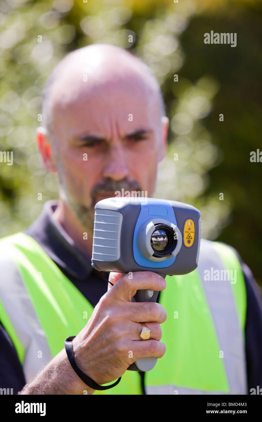 Un tecnico utilizza una termocamera per controllare l'efficienza termica di una casa e dove il calore viene Immagini Stock