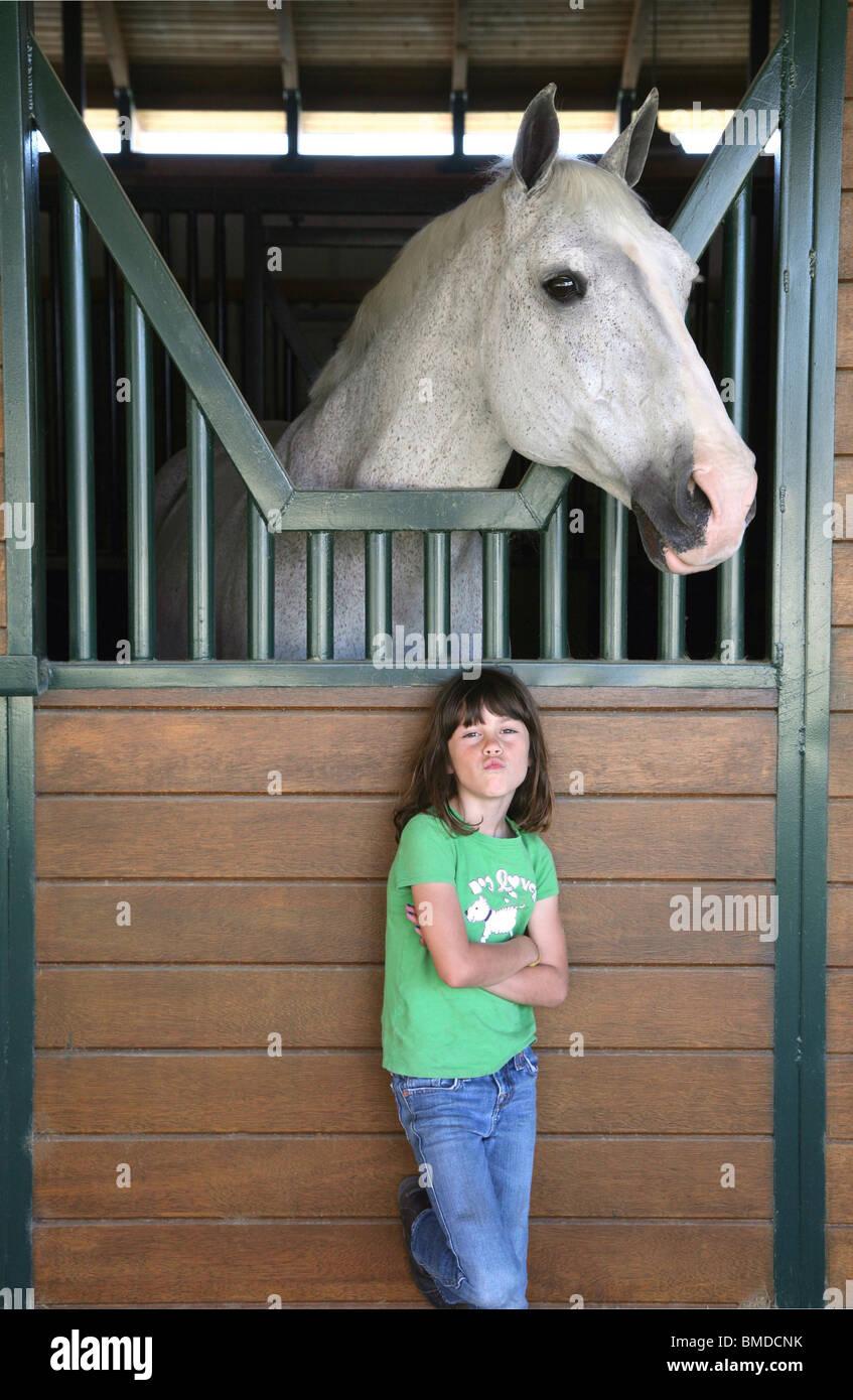 Giovane ragazza che sta sotto il cavallo in fienile Foto Stock