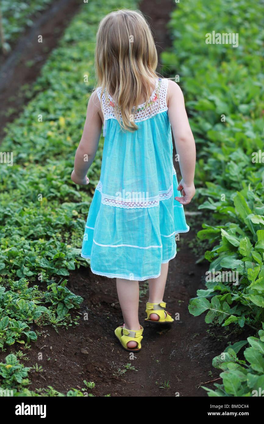Giovane ragazza in abito a piedi attraverso il campo di coltivazione Immagini Stock