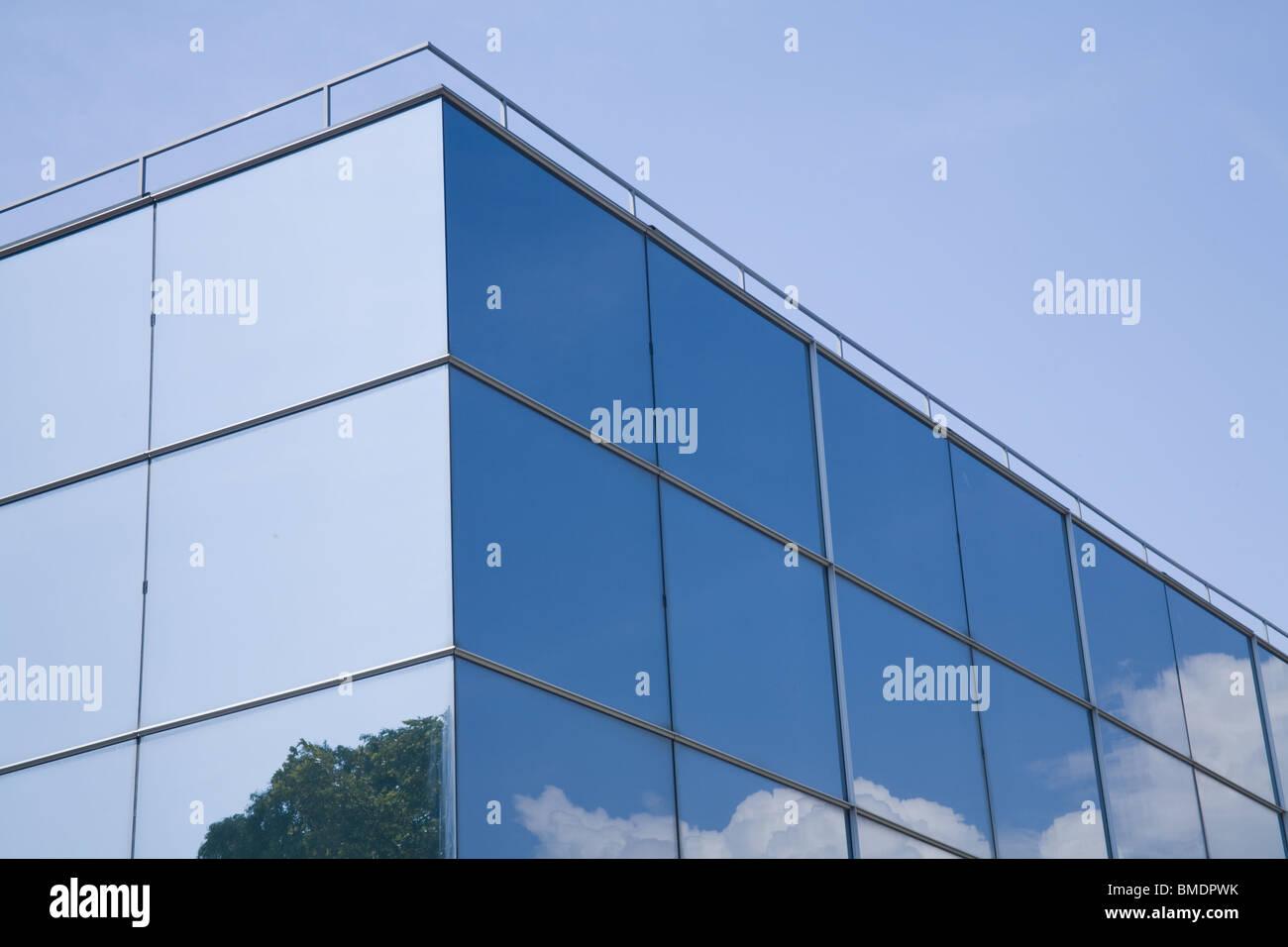 Moderno edificio di vetro con alberi e nuvole riflettono su di esso. Foto Stock