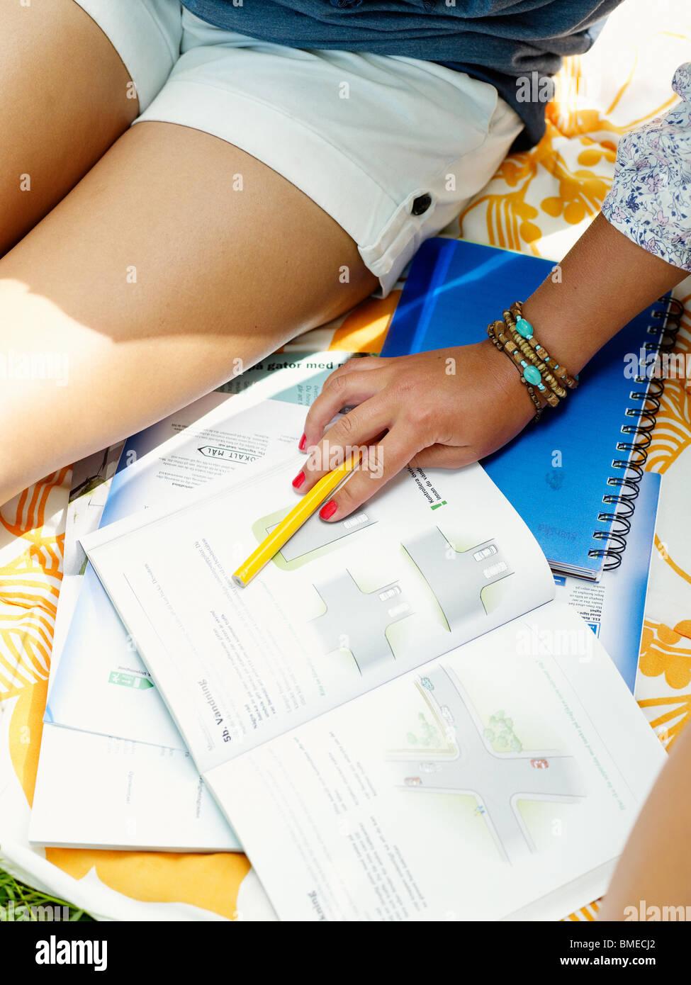 Donna seduta con il libro, vista in elevazione, close-up Immagini Stock
