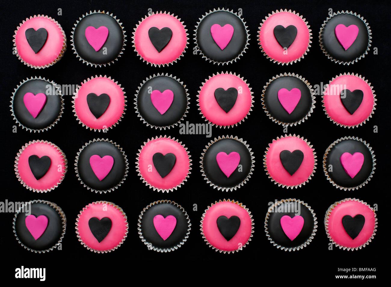 Mini Tortine decorate con nero e rosa ghiaccio e forme di cuore Immagini Stock