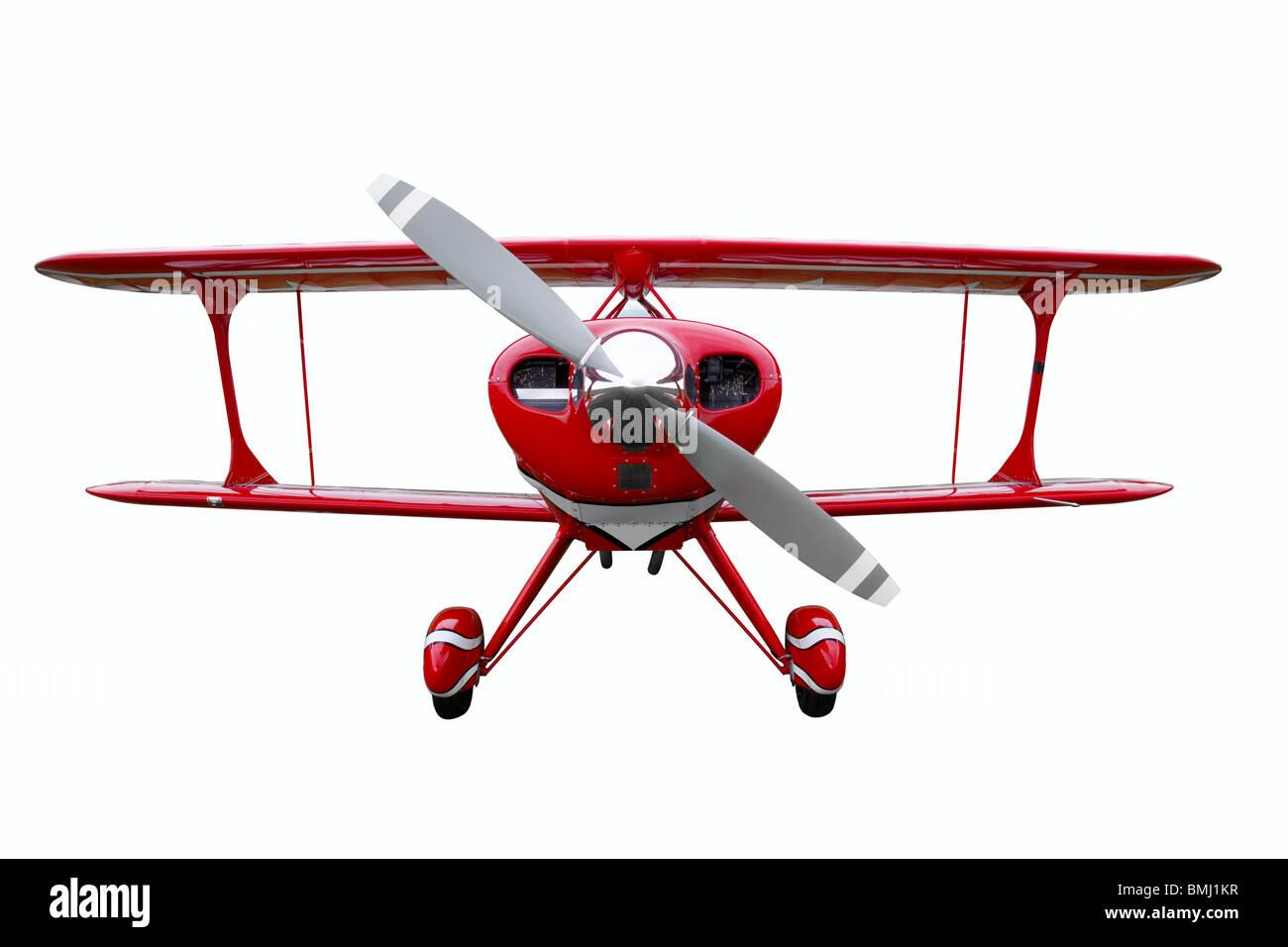 Un biplano rosso isolato su uno sfondo bianco. Immagini Stock