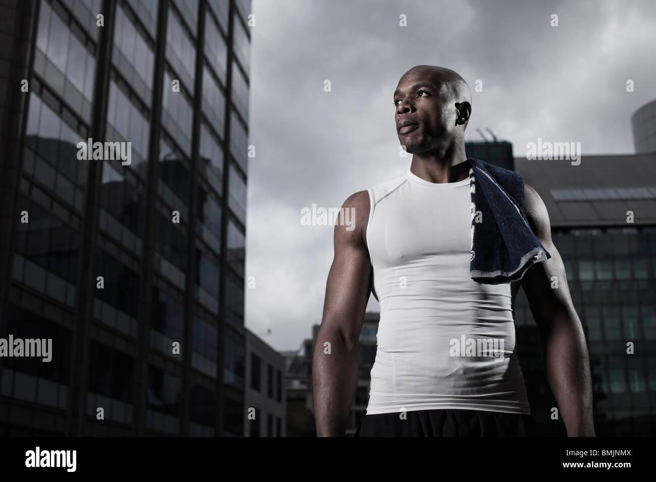 Montare l'uomo di indossare abbigliamento sportivo backgrounded dai moderni edifici della città Immagini Stock