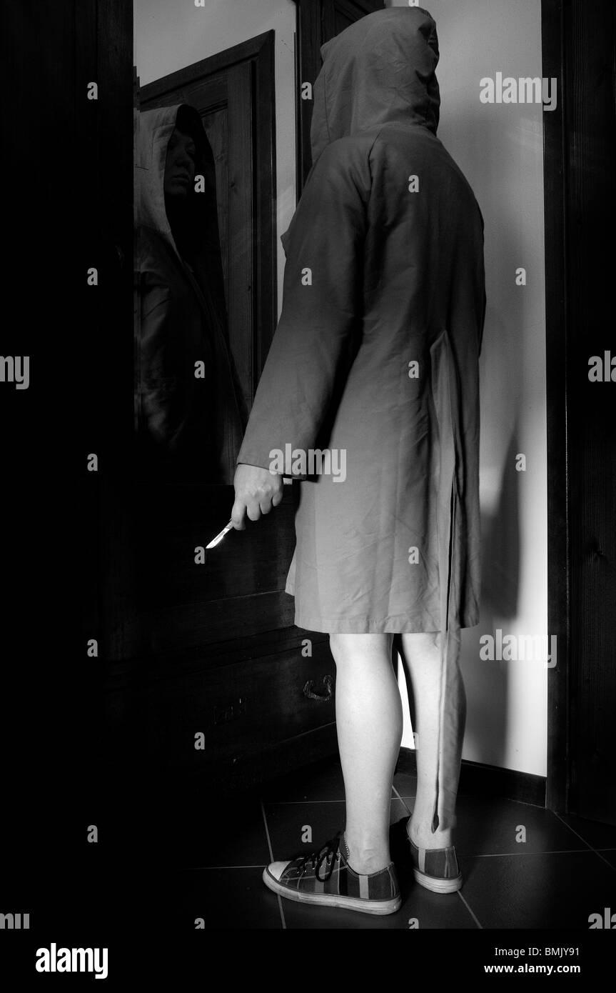 Donna con cappuccio con il coltello nella parte anteriore dello specchio Immagini Stock