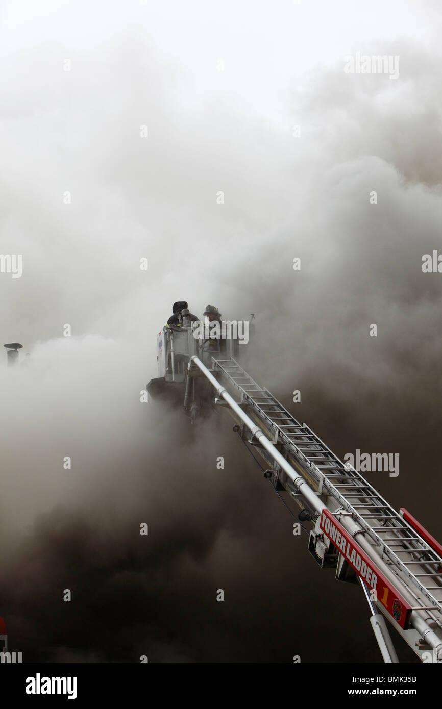 Firefighter combattendo un smoky blaze Foto Stock