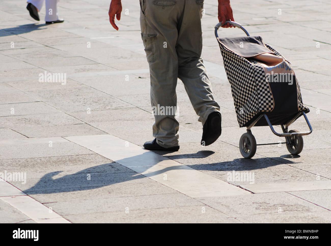 L'uomo tirando una shopping bag su ruote, Venezia, Italia Immagini Stock