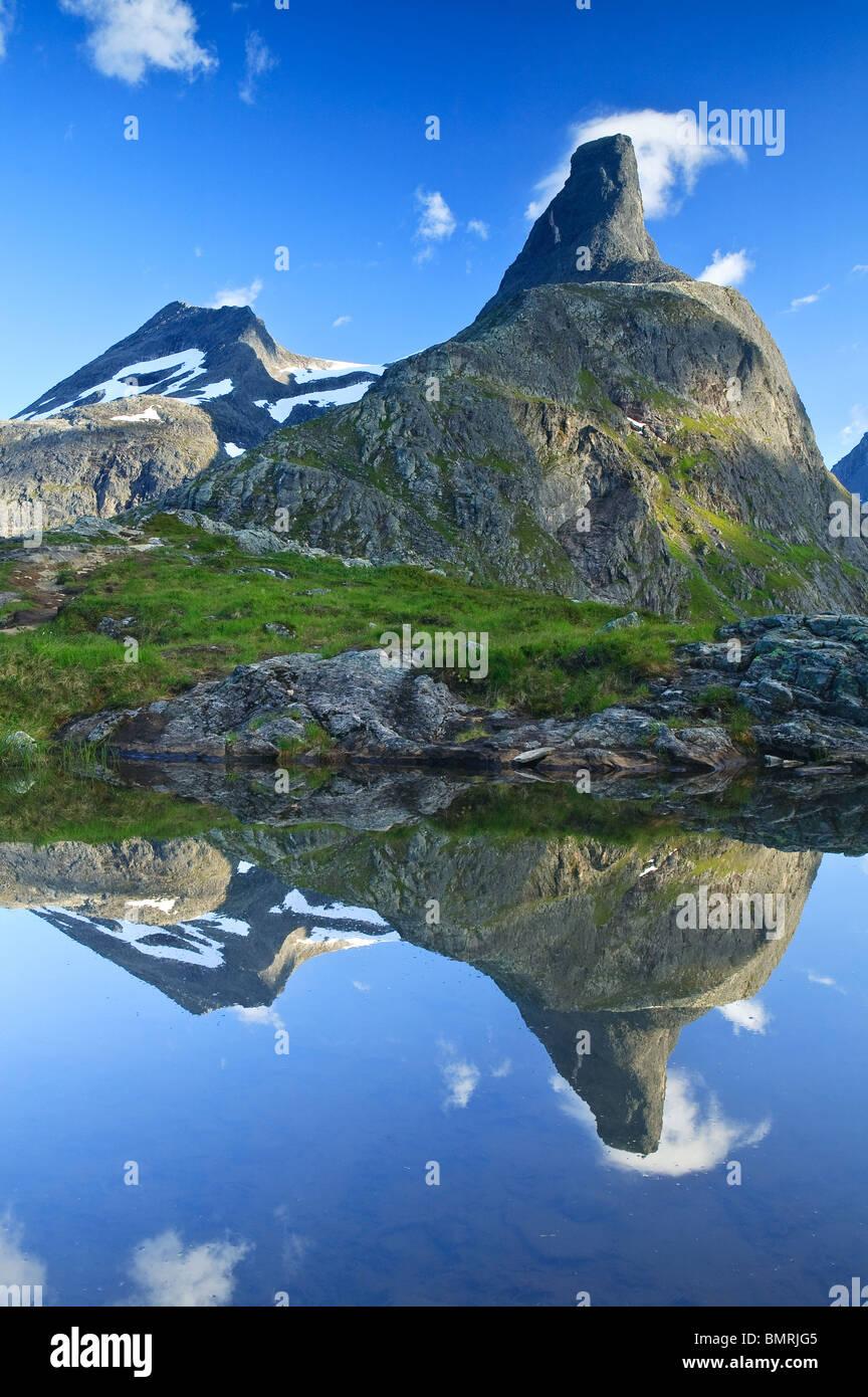 La montagna Romsdalshorn, 1550 m, che si riflette in un piccolo lago nella valle Romsdalen, Rauma kommune, Møre og Romsdal, Norvegia. Foto Stock