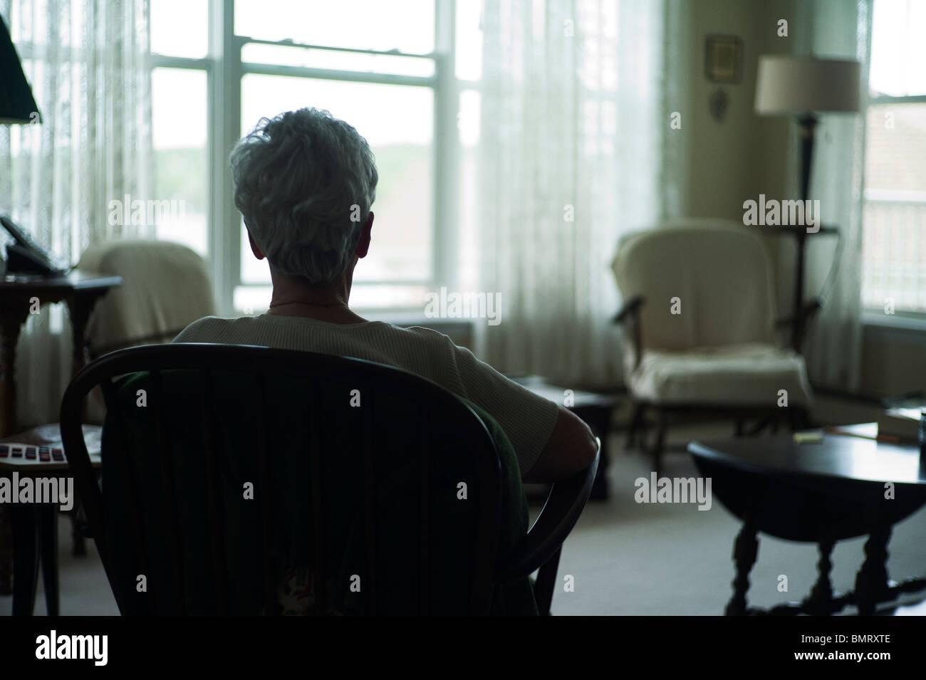 Vecchia donna da dietro come si siede a guardare fuori dalla finestra. Immagini Stock