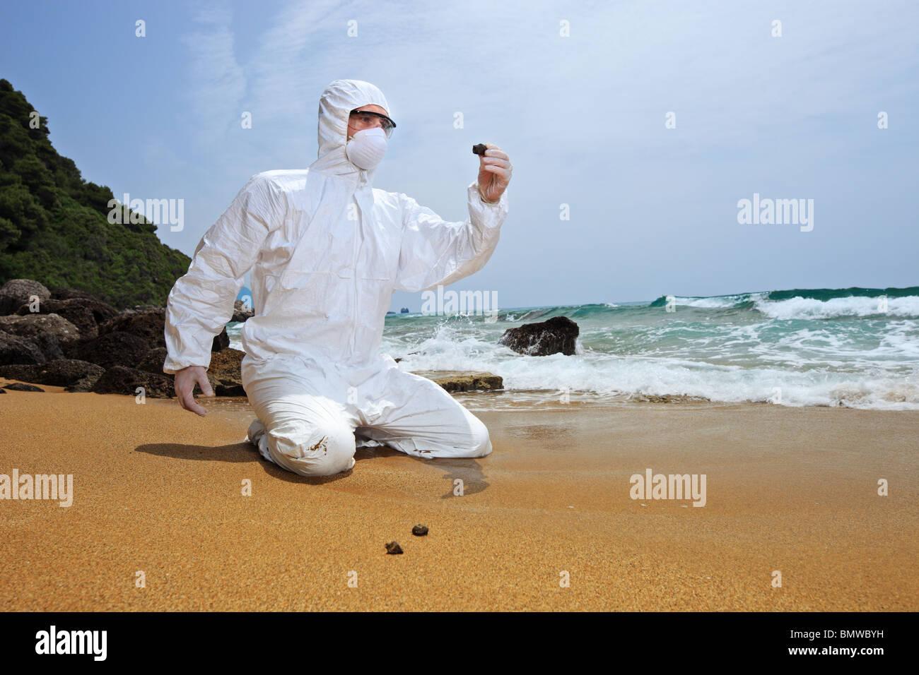 Lavoratore in una tuta protettiva esaminando l'inquinamento in spiaggia Immagini Stock