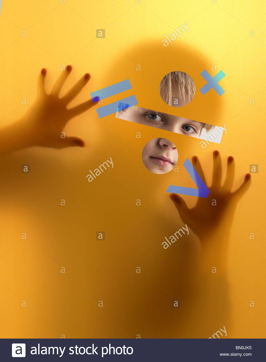 Un ragazzo coetanei attraverso uno schermo coperto di simboli di matematica Immagini Stock