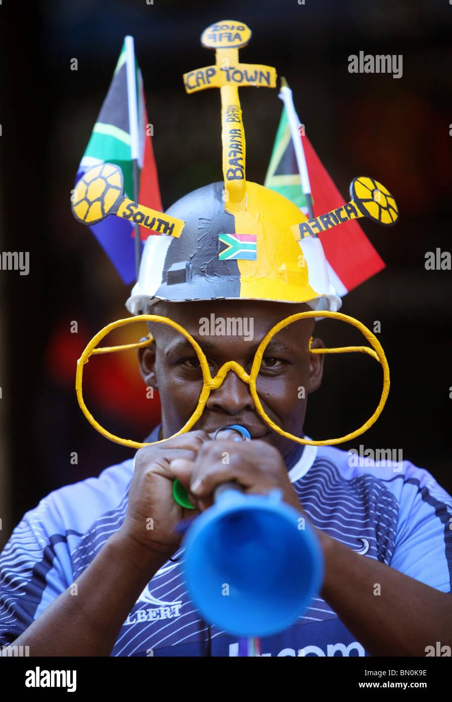 South African soccer ventilatore soffia la sua Vuvuzelas a Cape Town. Immagini Stock