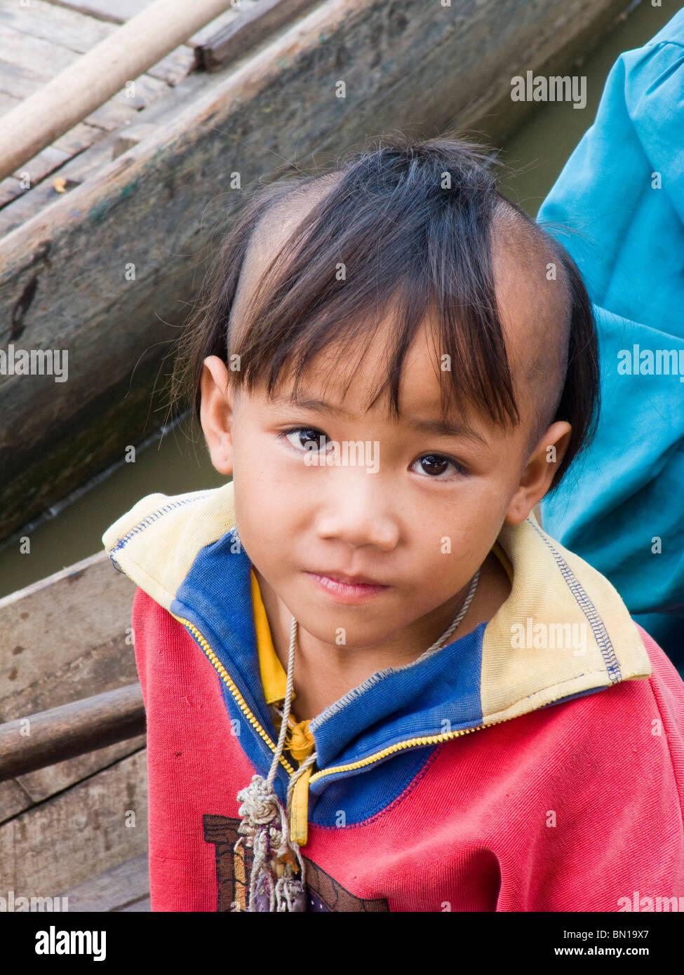 Ragazzo con parzialmente testa rasata, Chong Khneas villaggio galleggiante, Lago Tonle Sap, Siam Reap, Cambogia Immagini Stock