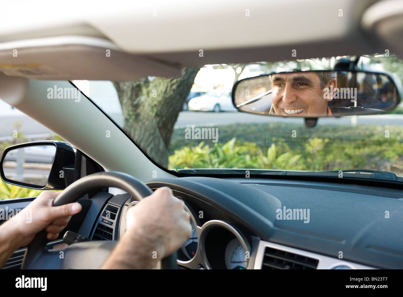 Uomo alla guida e la riflessione in specchietto retrovisore Immagini Stock