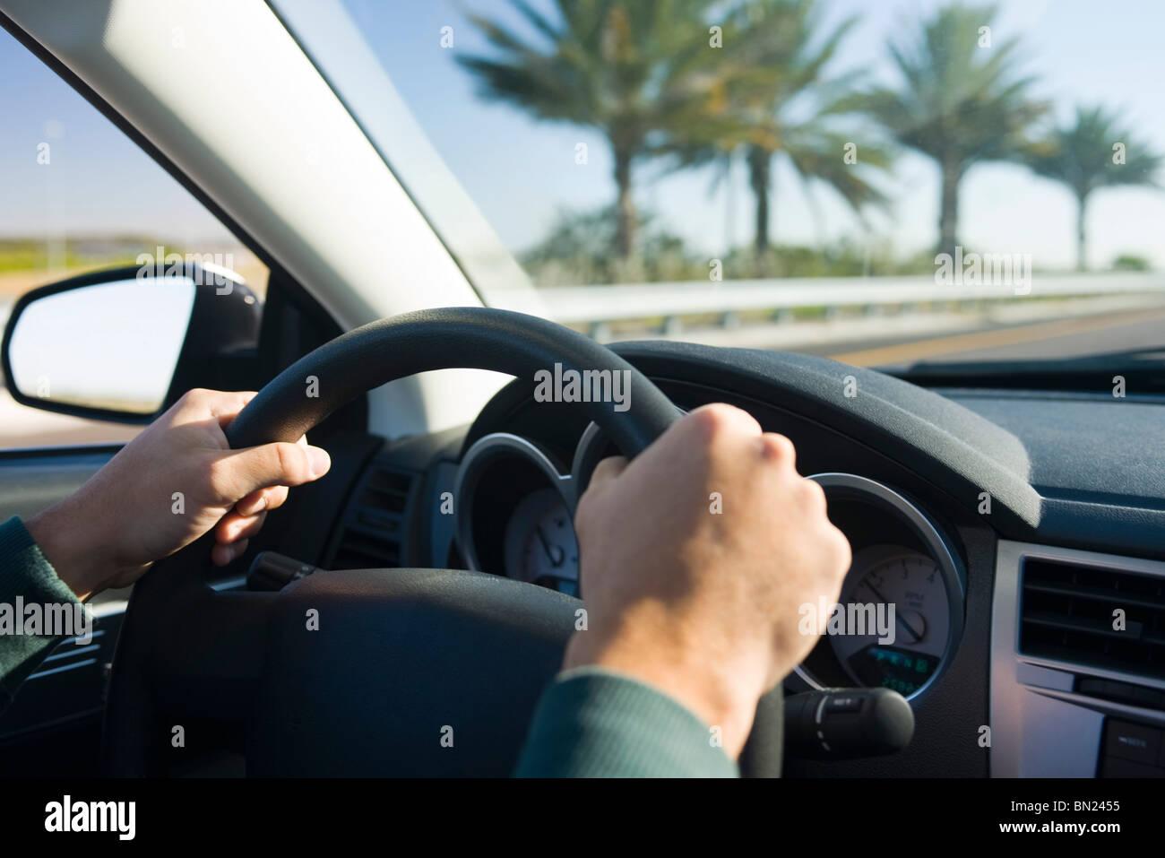 La guida con entrambe le mani sul volante Immagini Stock