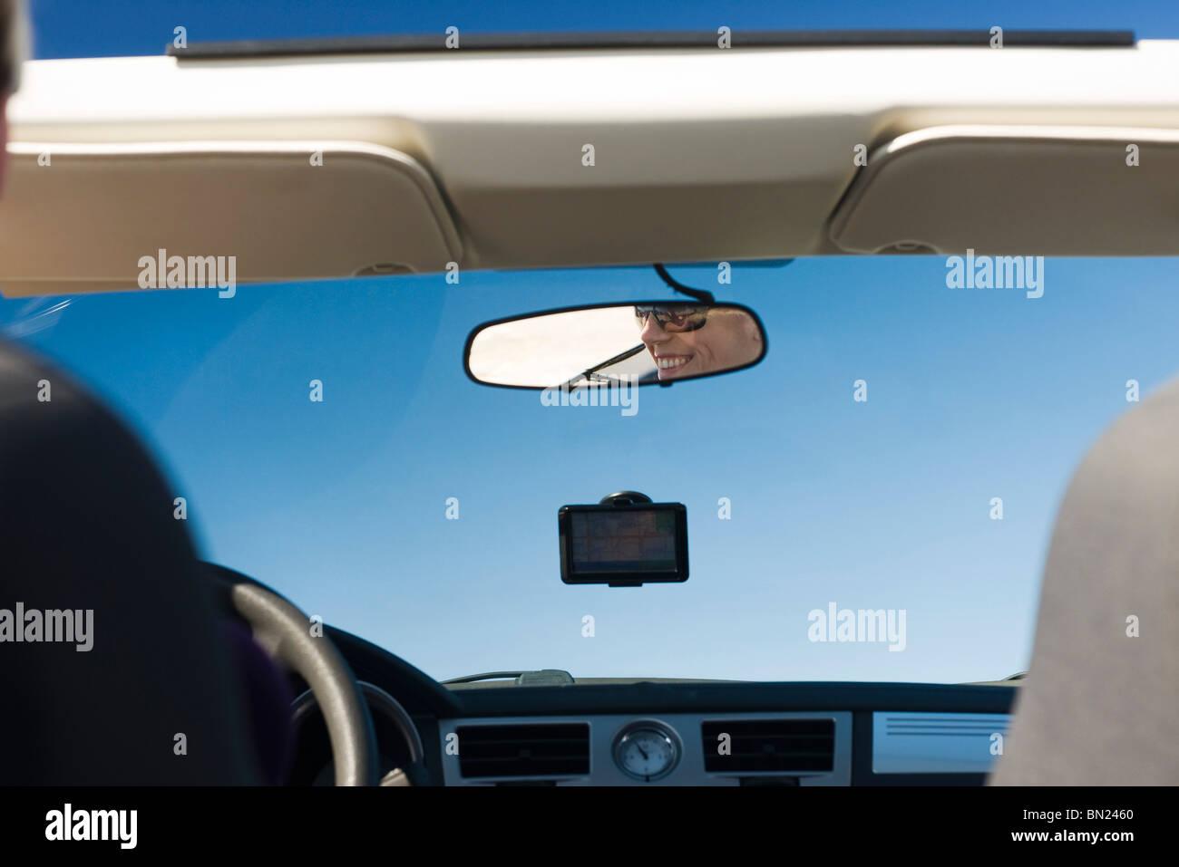 Donna alla guida di auto e la riflessione in specchietto retrovisore Immagini Stock