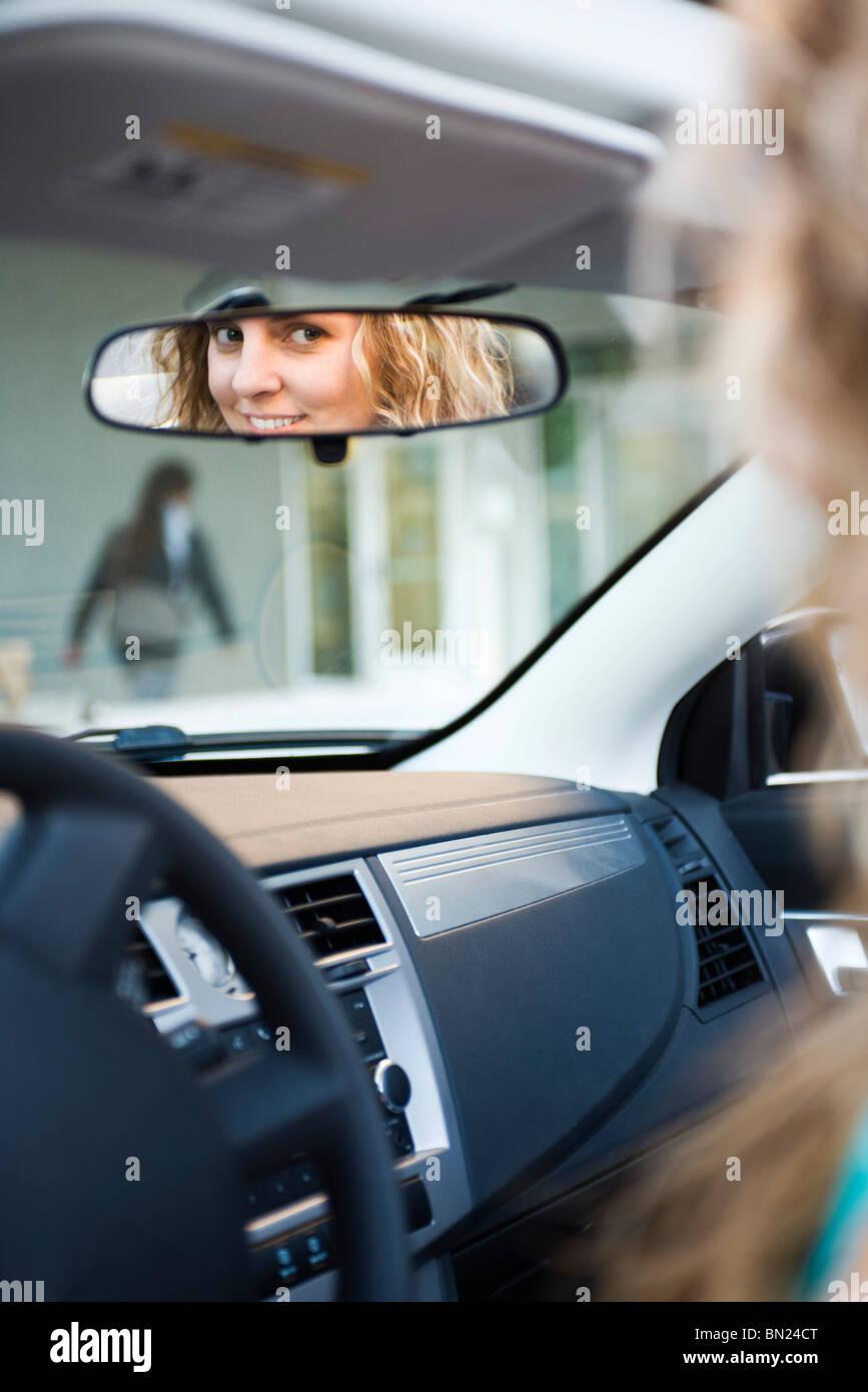 Donna alla guida e la riflessione in specchietto retrovisore Immagini Stock