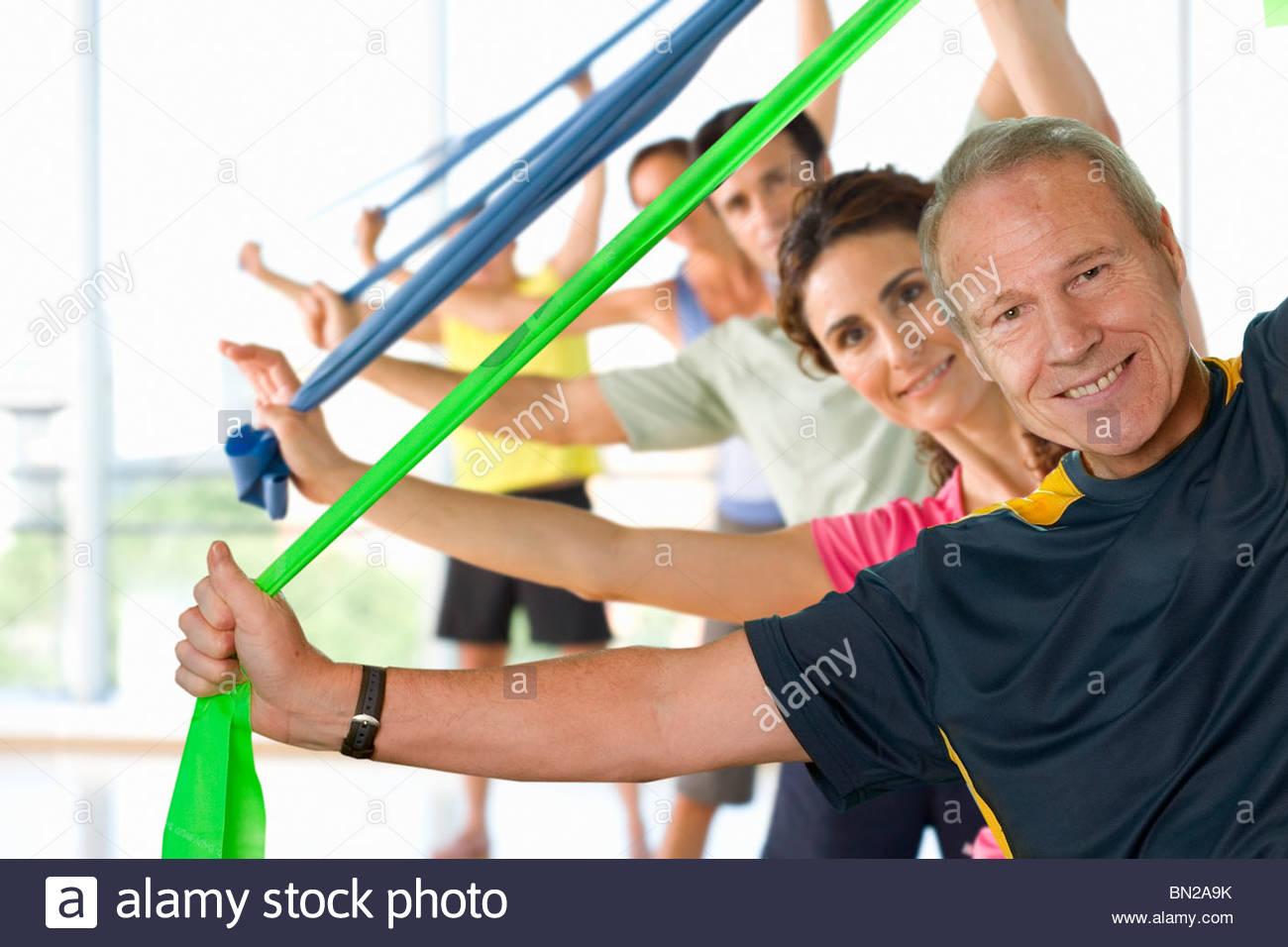 Gli uomini e le donne di contenimento bande di resistenza overhead in vetro di esercizio Immagini Stock