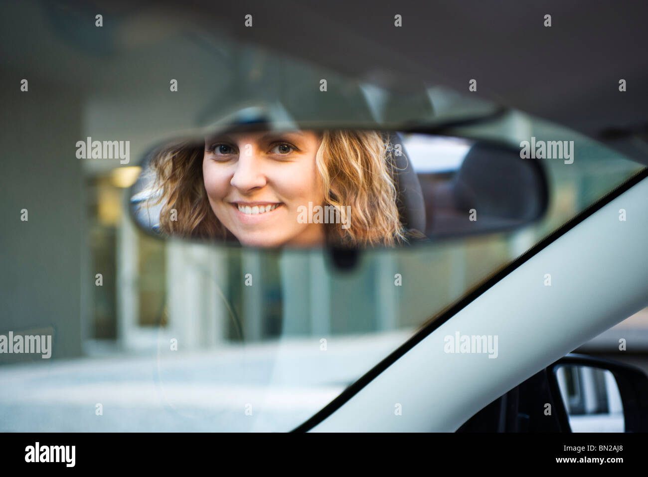 Volto di donna riflessa in specchietto retrovisore Immagini Stock