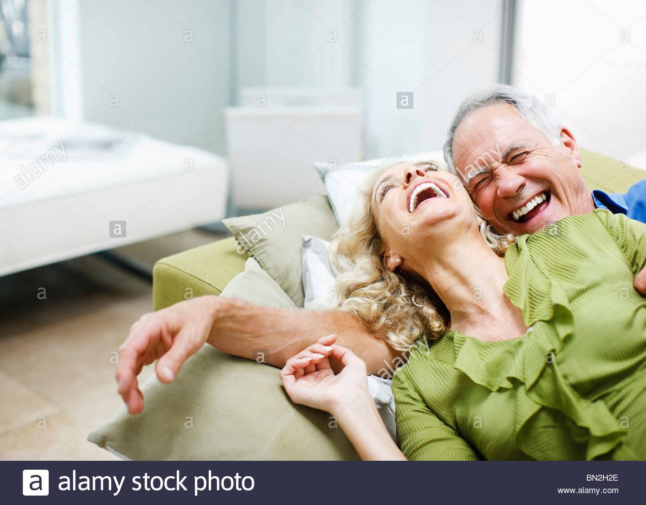 Accoppiare la posa sul divano insieme Immagini Stock
