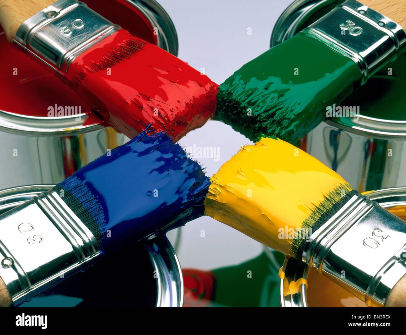 Close-up di quattro pennelli su barattoli di vernice Immagini Stock