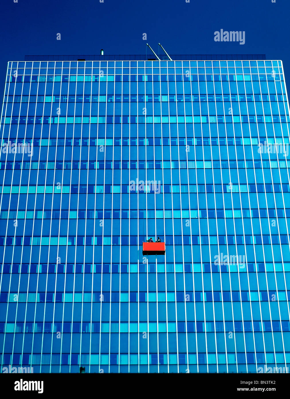 Basso angolo vista di due persone nel cestello la pulizia di vetri, Germania Immagini Stock