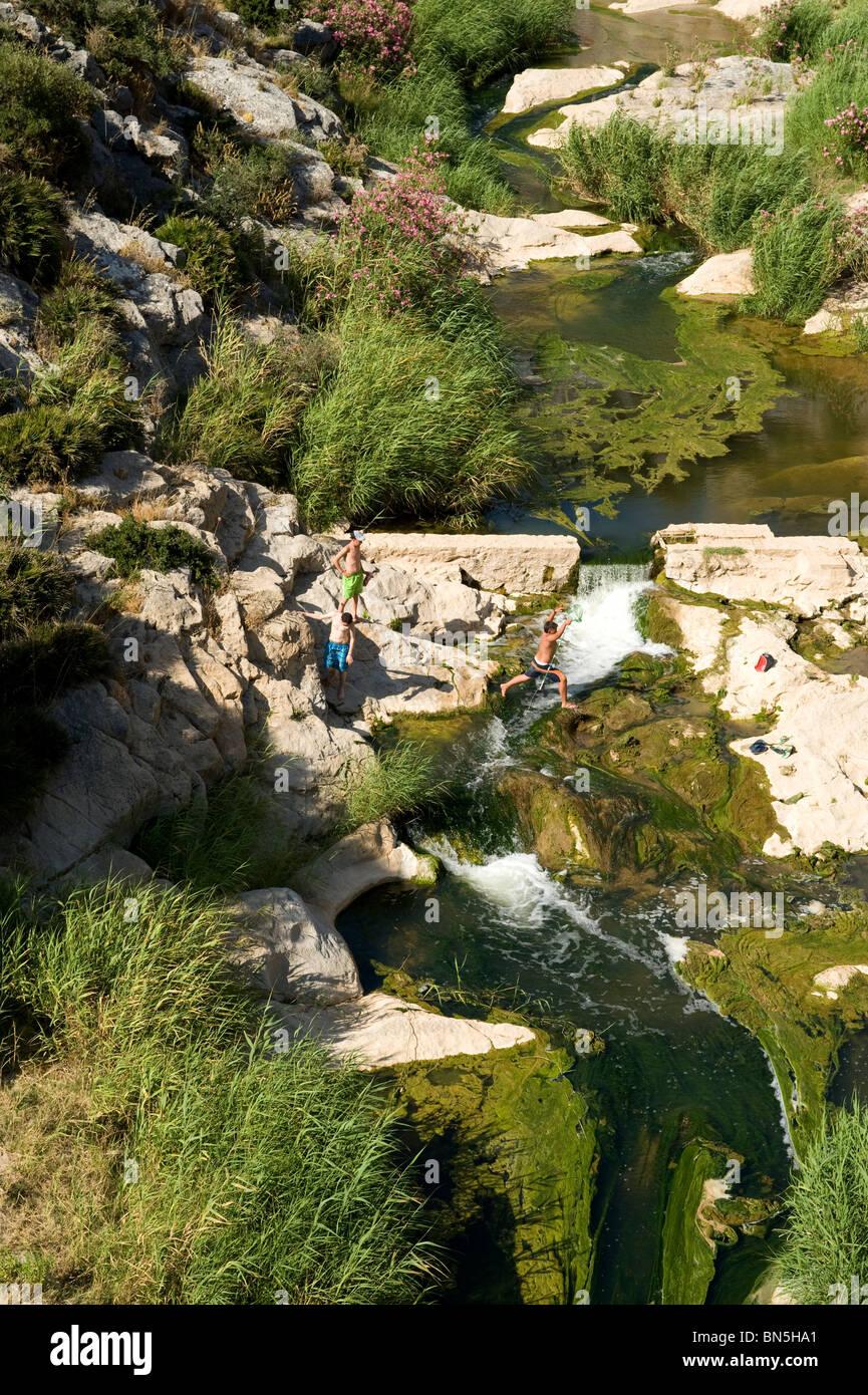Ragazzo di saltare attraverso piccolo fiume che scorre nella gola con piccole cascate e piscine di roccia. Immagini Stock