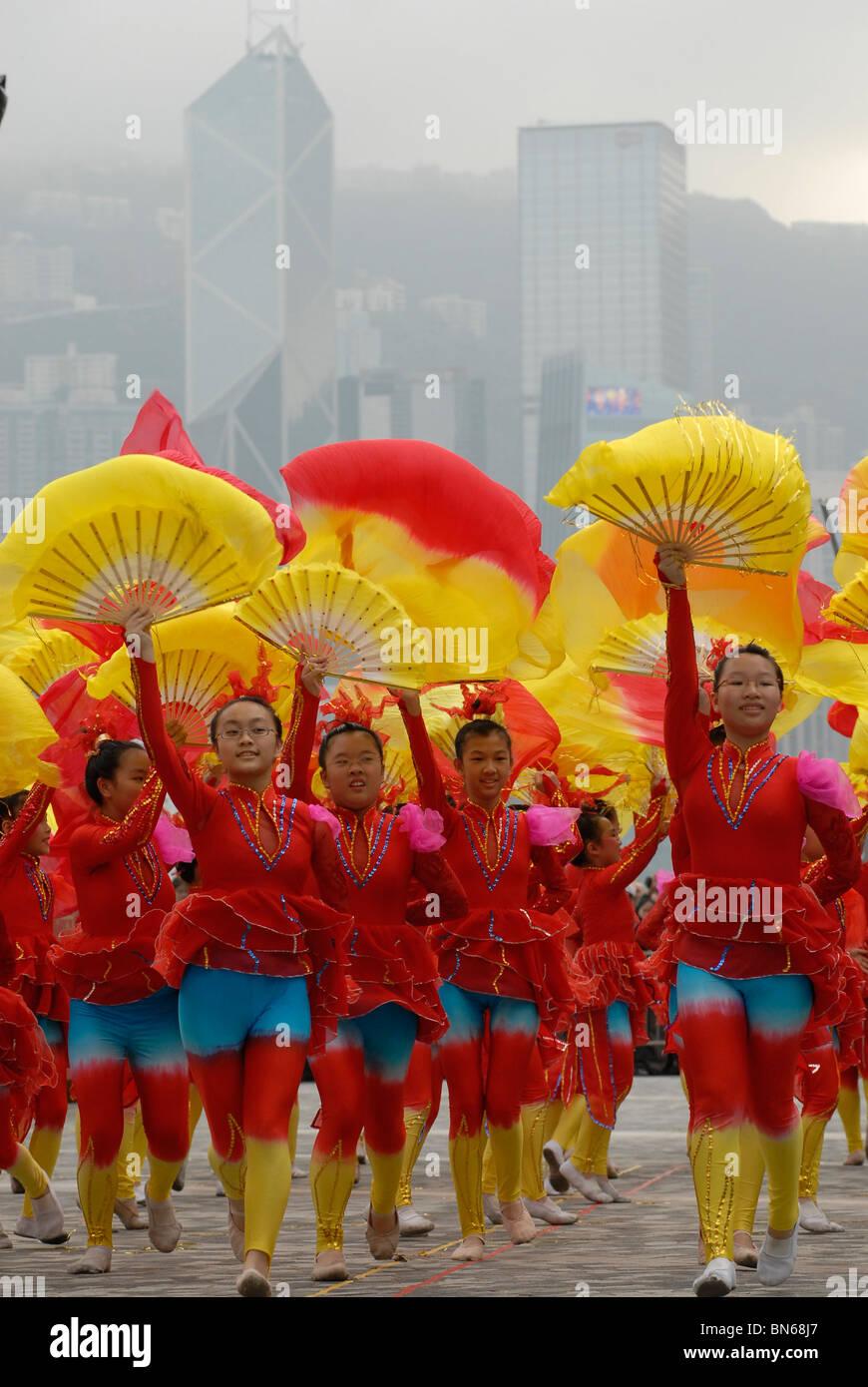 Giovani ragazze cinesi in abiti di festa ballando durante il nuovo anno lunare cinese celebrazioni in Kowloon, Hong Immagini Stock