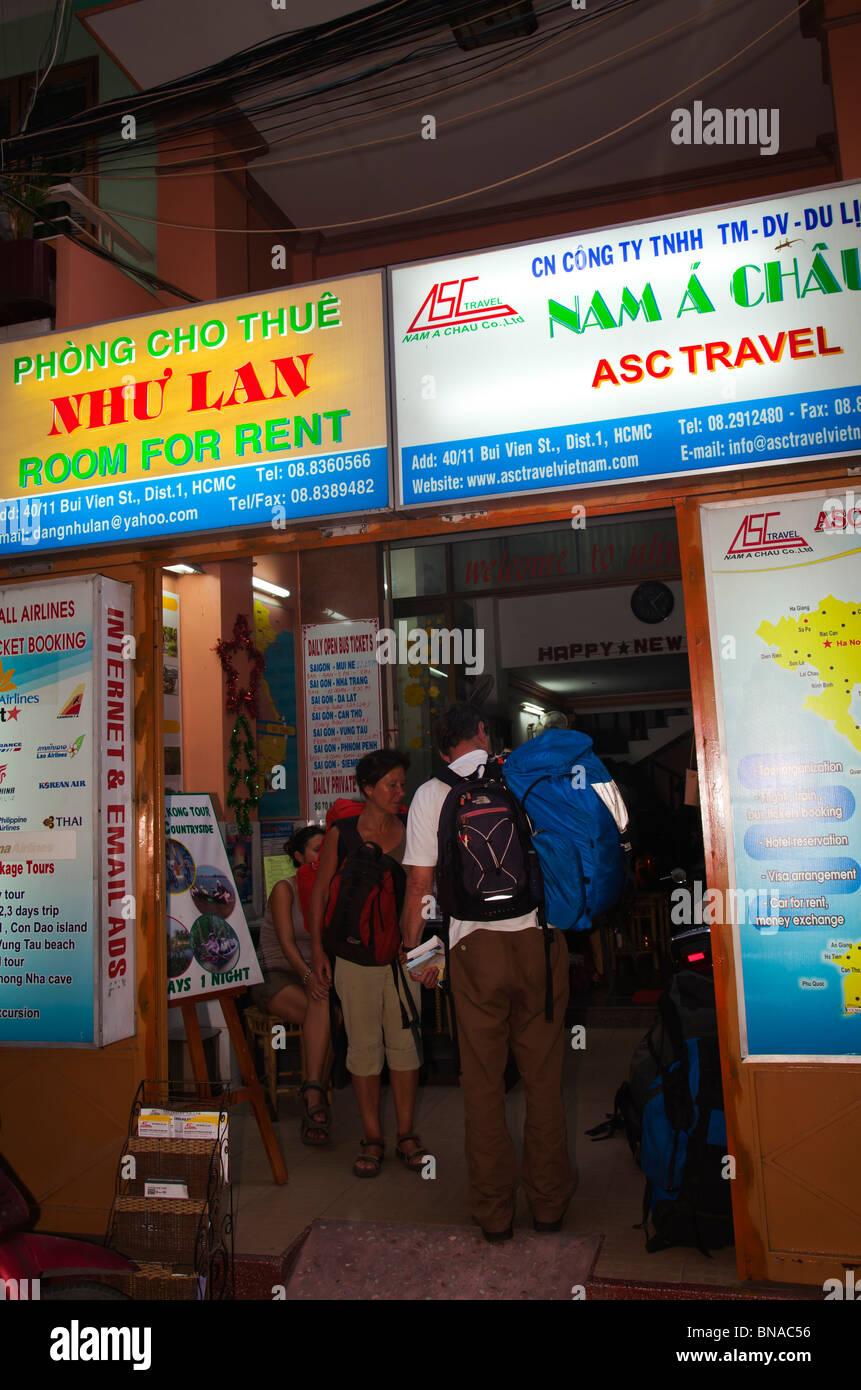I turisti backpackers in hotel e agente di viaggio per ufficio da notte Immagini Stock