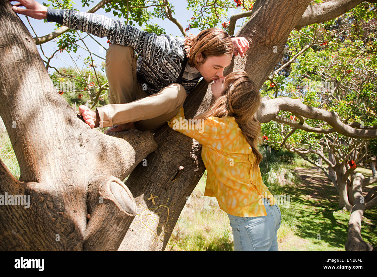 L uomo nella struttura ad albero appoggiandosi a kiss ragazza Immagini Stock