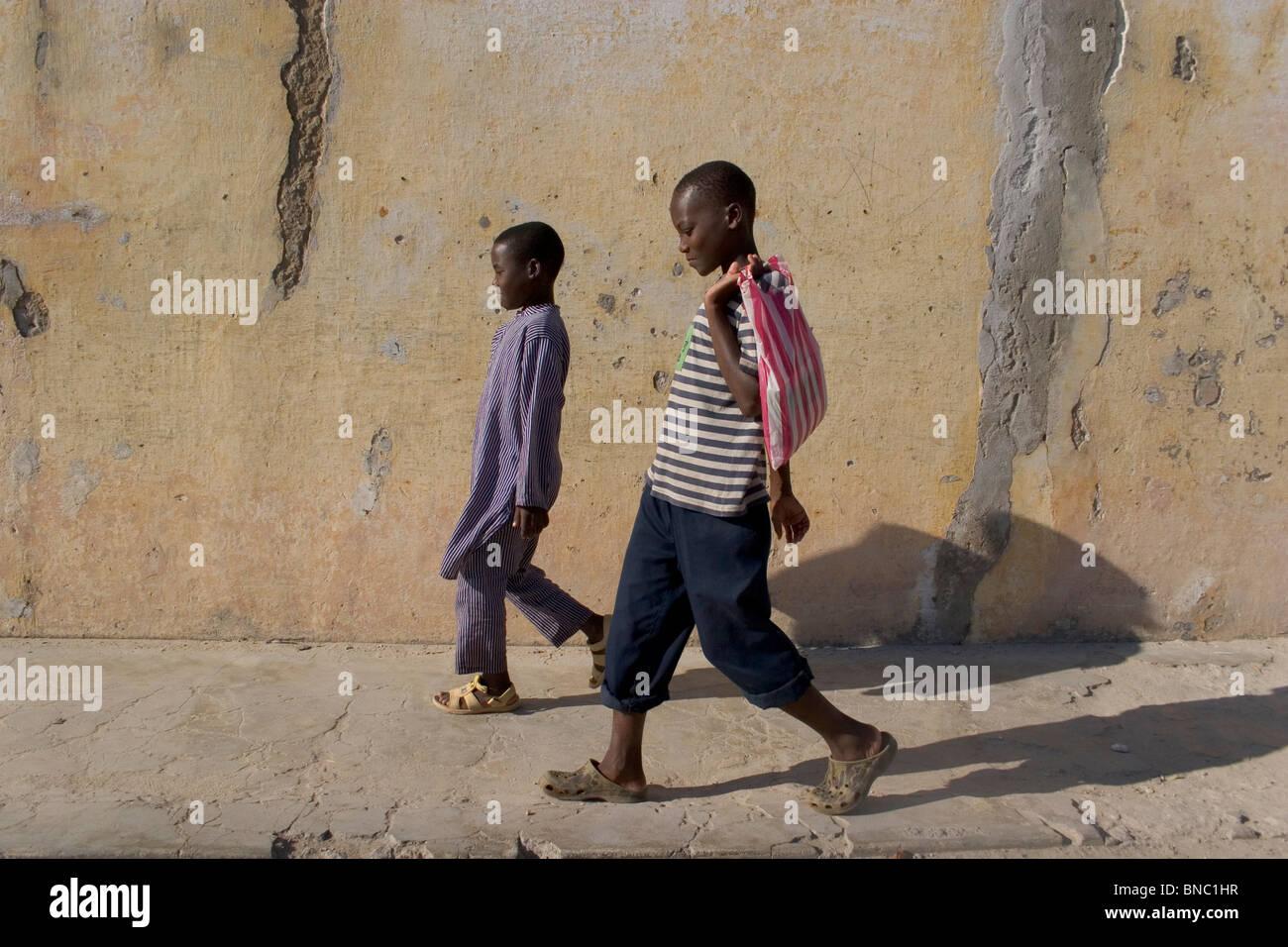 I ragazzi del Mozambico a piedi lungo la strada, Ilha de Mozambico. Immagini Stock