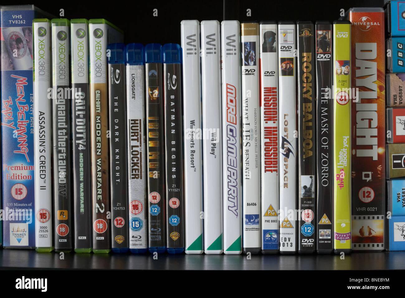 Fila di vhs dvd blu-ray video e casi di Wii e xbox360 video giochi su un ripiano nel Regno Unito Immagini Stock