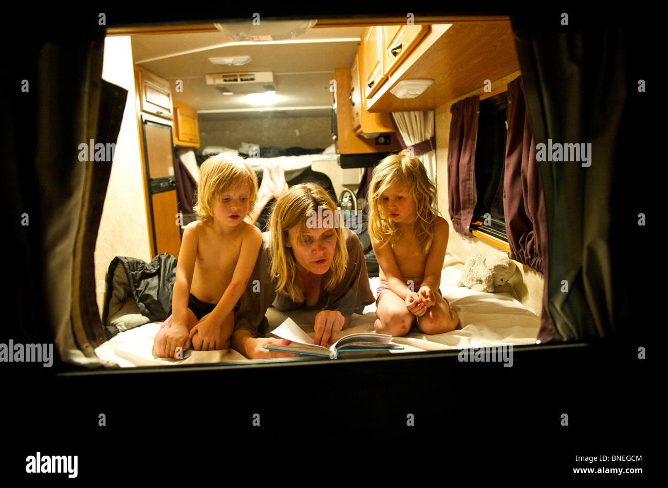 Madre la lettura di una storia prima di addormentarsi per i suoi figli in un camper RV in Texas, Stati Uniti d'America Foto Stock