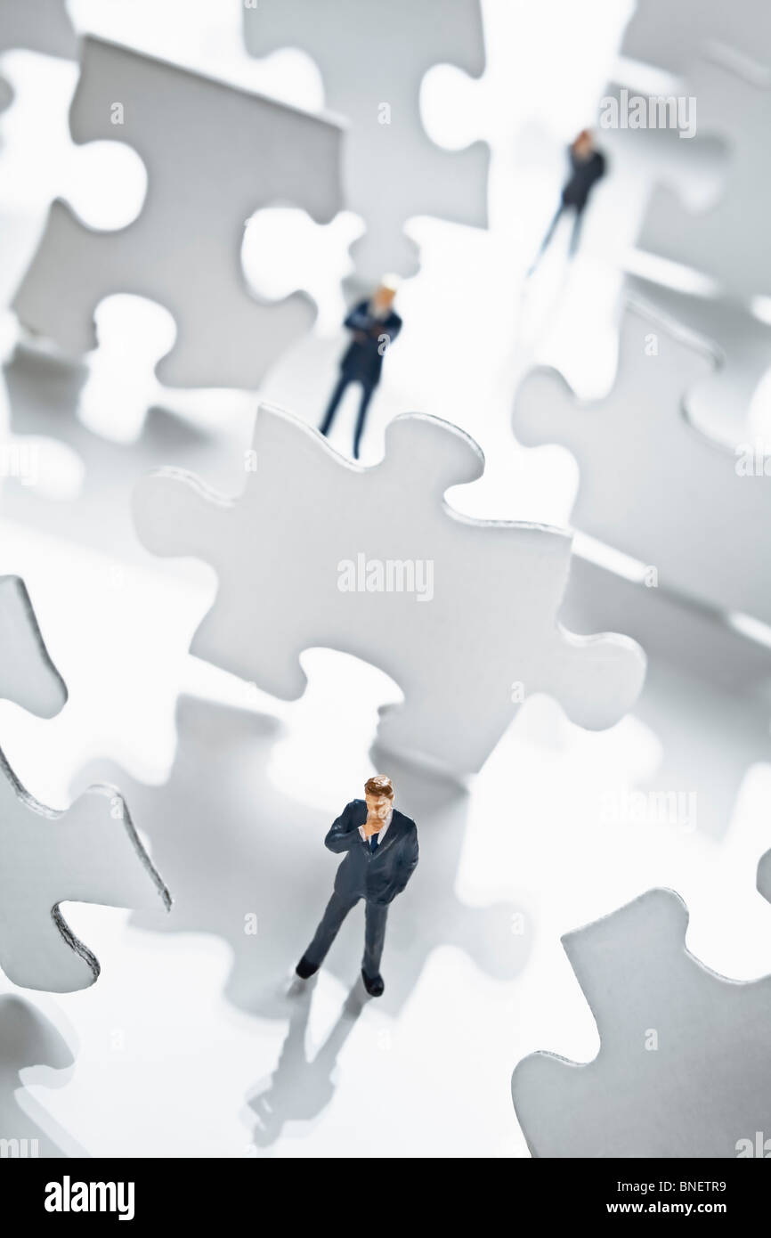 Imprenditore figurina circondato da pezzi di un puzzle Immagini Stock