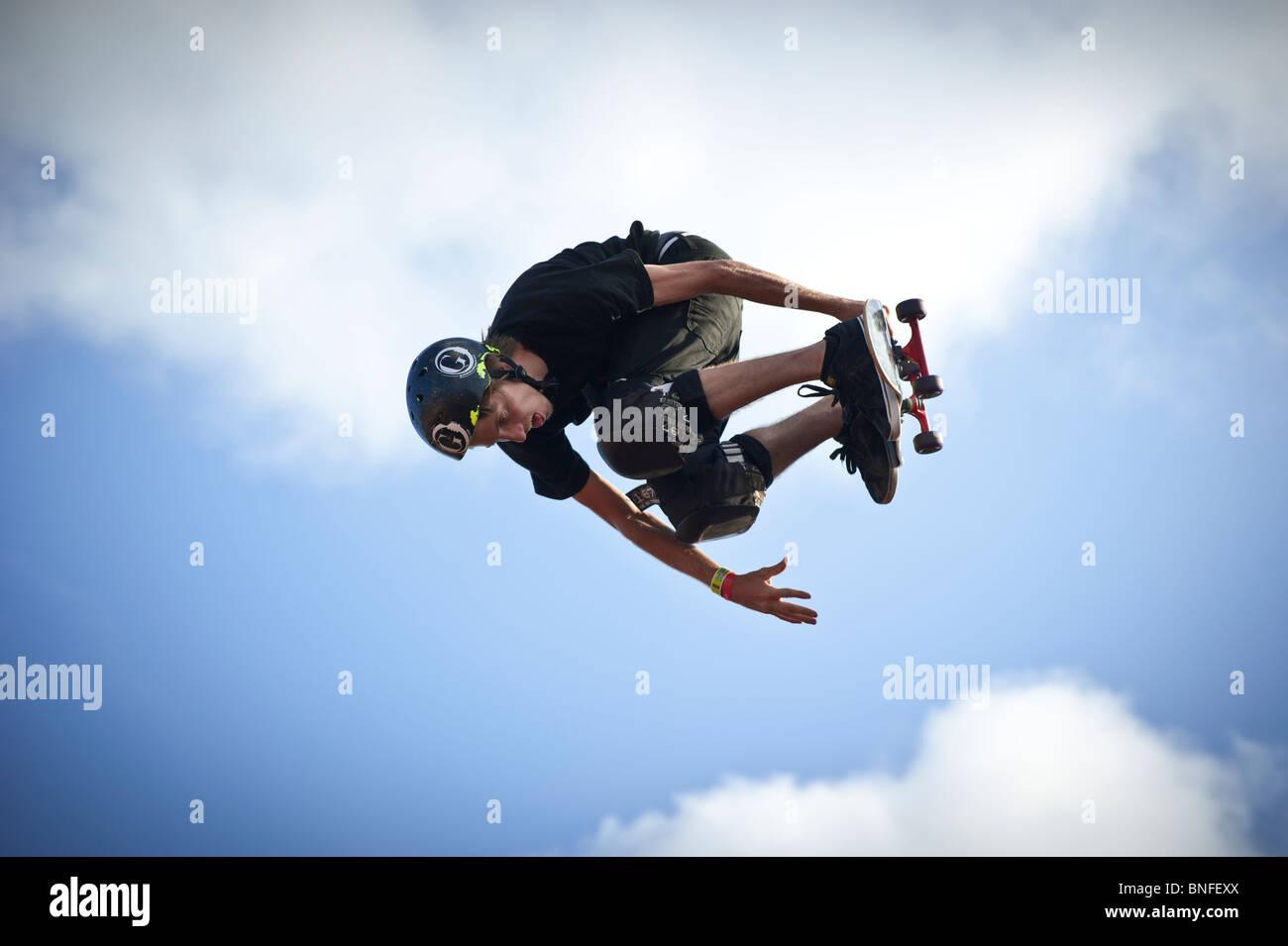 Lo skateboarder professionista di saltare in aria. Immagini Stock