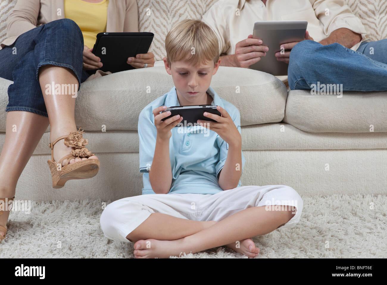 Ragazzo e i genitori di sedersi con i dispositivi portatili Immagini Stock