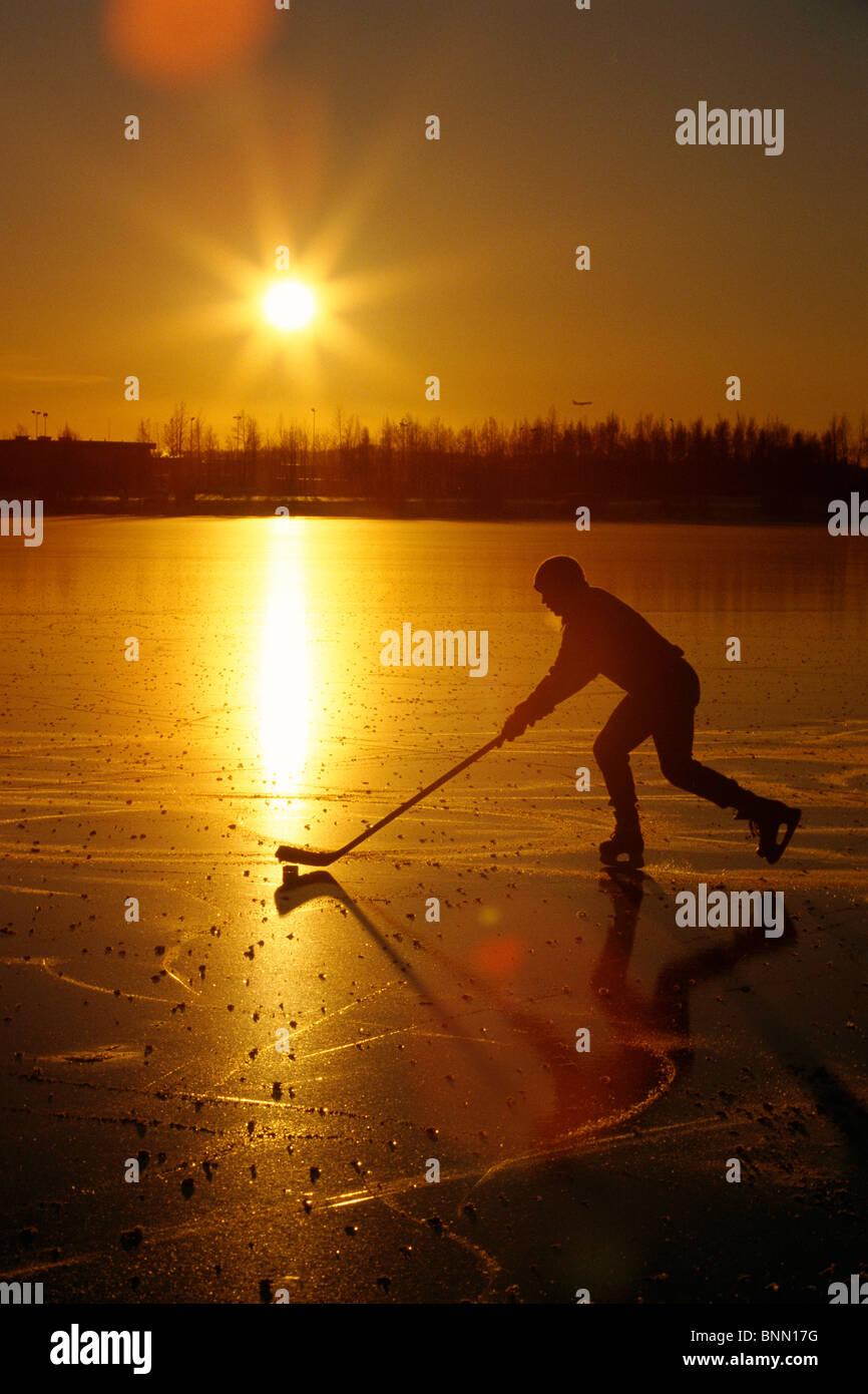 Persona di giocare ad hockey al lago Hood Anchorage AK SC inverno scenic Immagini Stock
