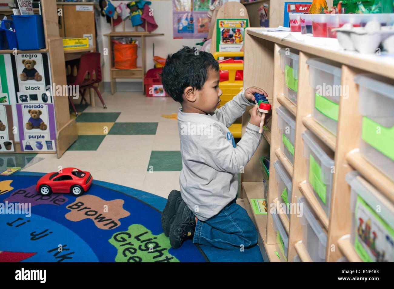 Ragazzo di età prescolare cercando un giocattolo sul ripiano in aula Immagini Stock