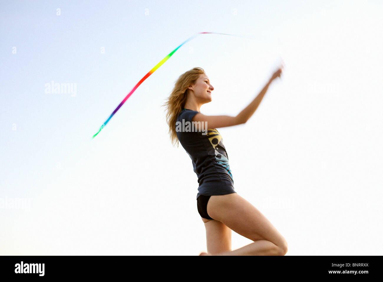 Giovane donna gioca con un nastro colorato in spiaggia. Immagini Stock