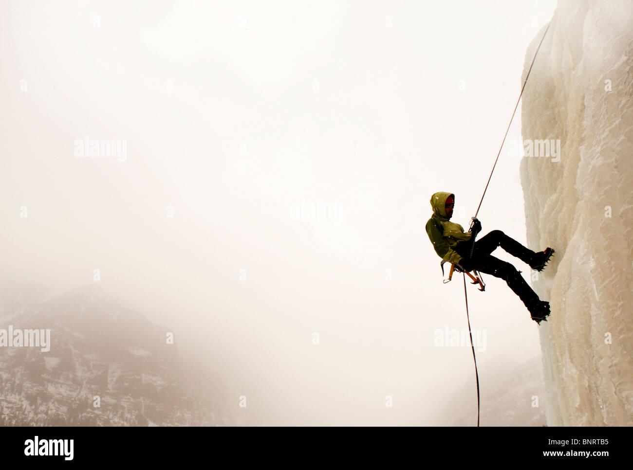 Un uomo di arrampicata su ghiaccio. Immagini Stock