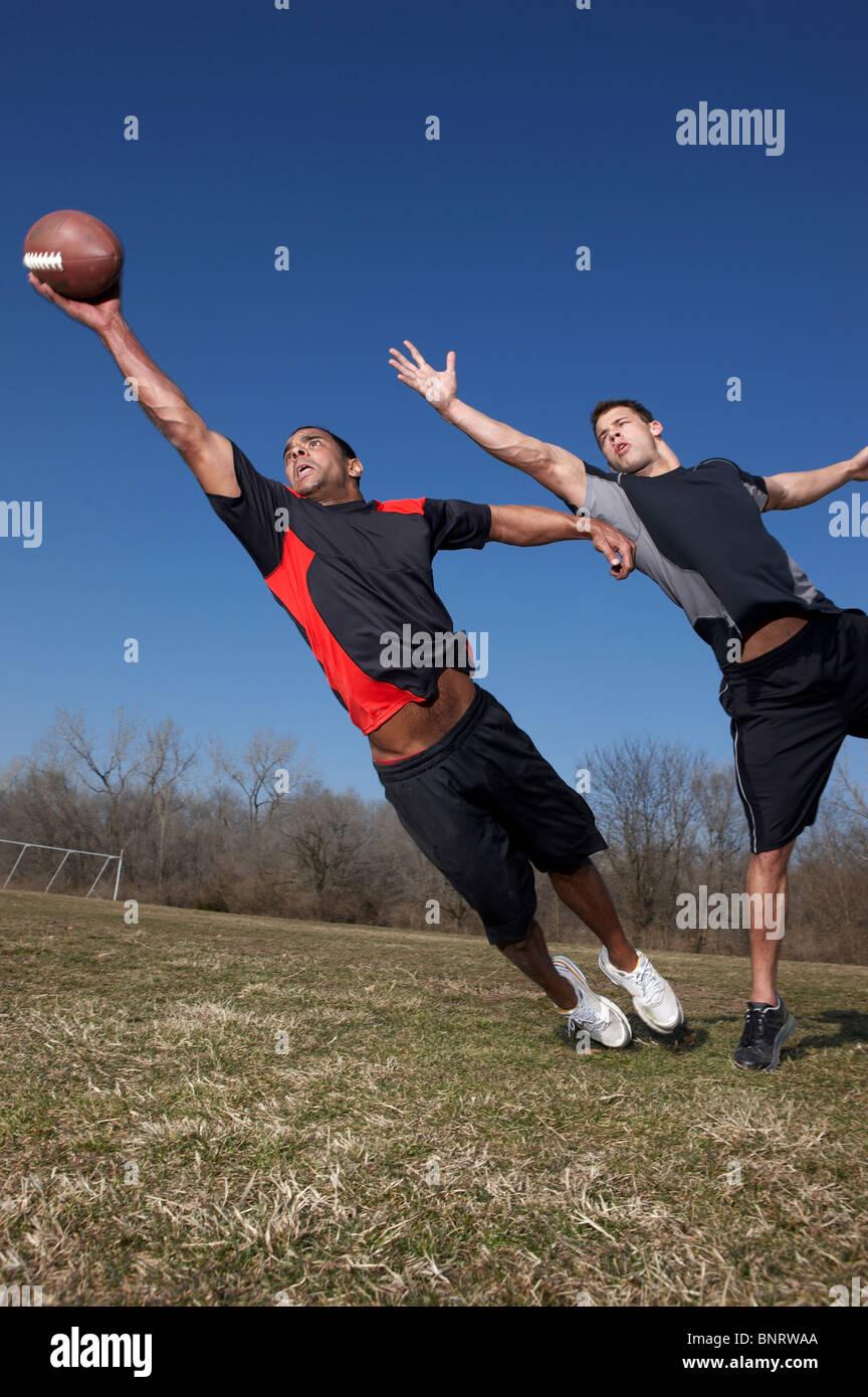 Due uomini di competere per un passaggio in un tocco del gioco del calcio. Immagini Stock