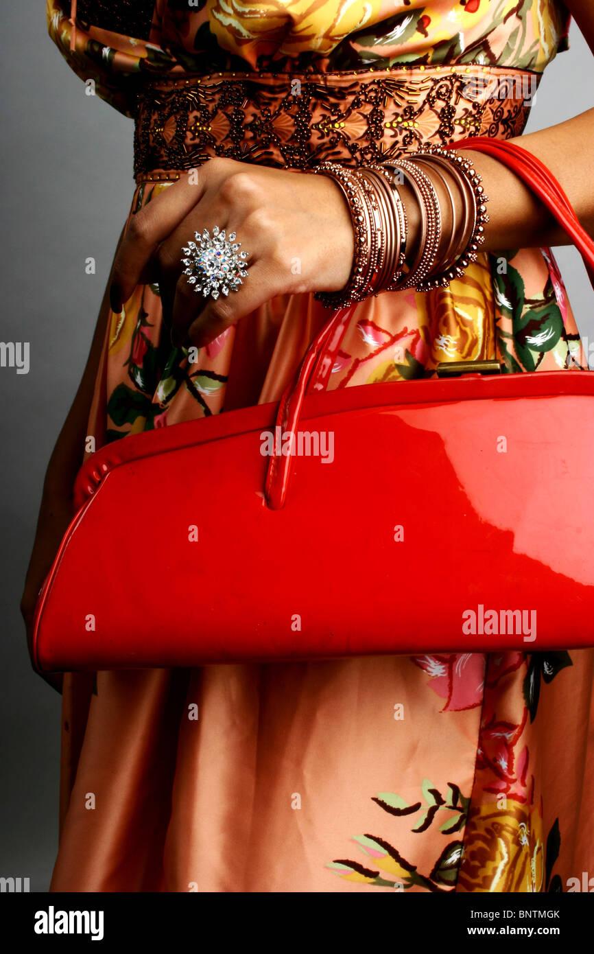 Donna che mantiene luminoso rosso portamonete che indossa una grande corona Foto Stock