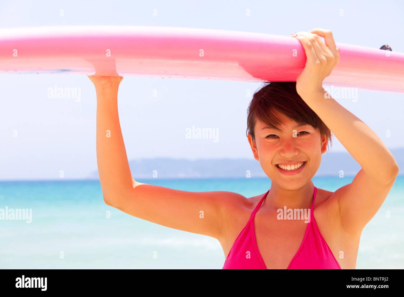 Ritratto di una giovane donna con una tavola da surf Immagini Stock