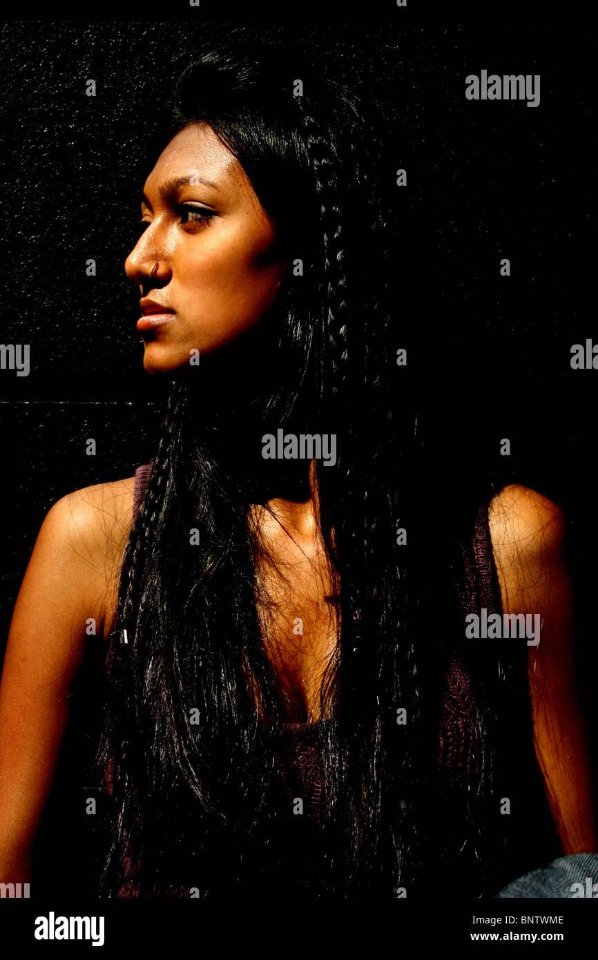 Giovane donna con capelli lunghi cercando di lato. Foto Stock