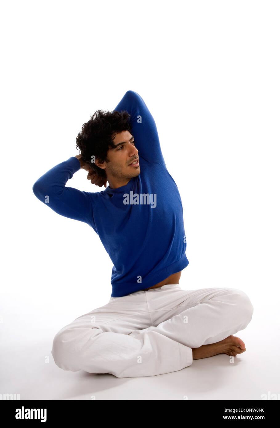 Uomo con gambe incrociate stretching corpo superiore Immagini Stock