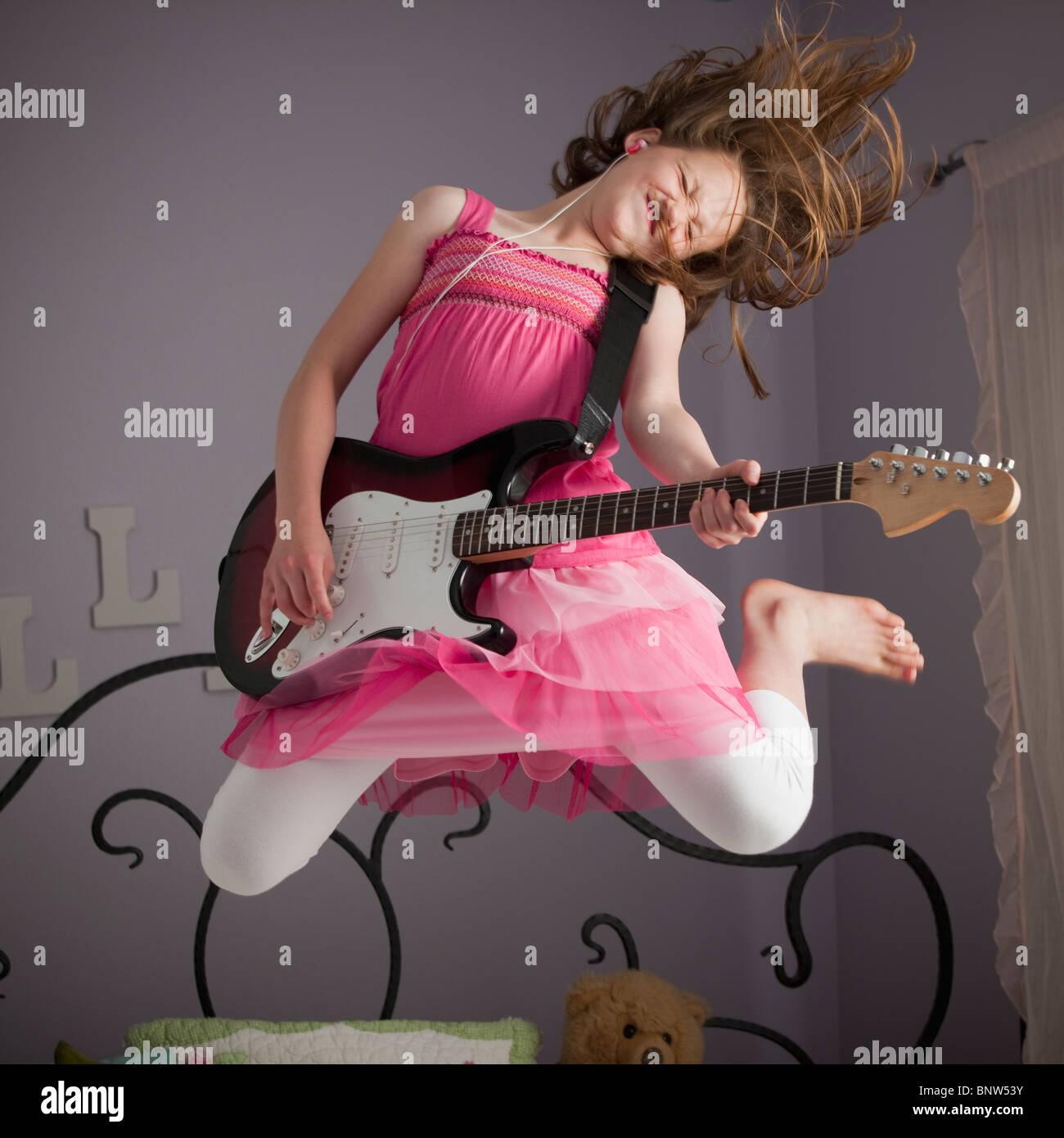 Le giovani ragazze a suonare la chitarra sul suo letto Immagini Stock
