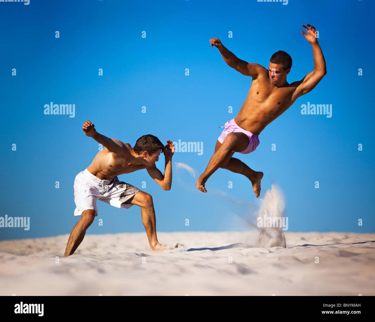 Due giovani uomini sport combattimenti sulla spiaggia. Immagini Stock