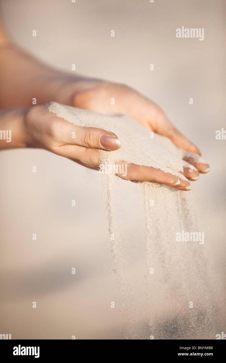 Giovane donna con sabbia in mani. Immagini Stock