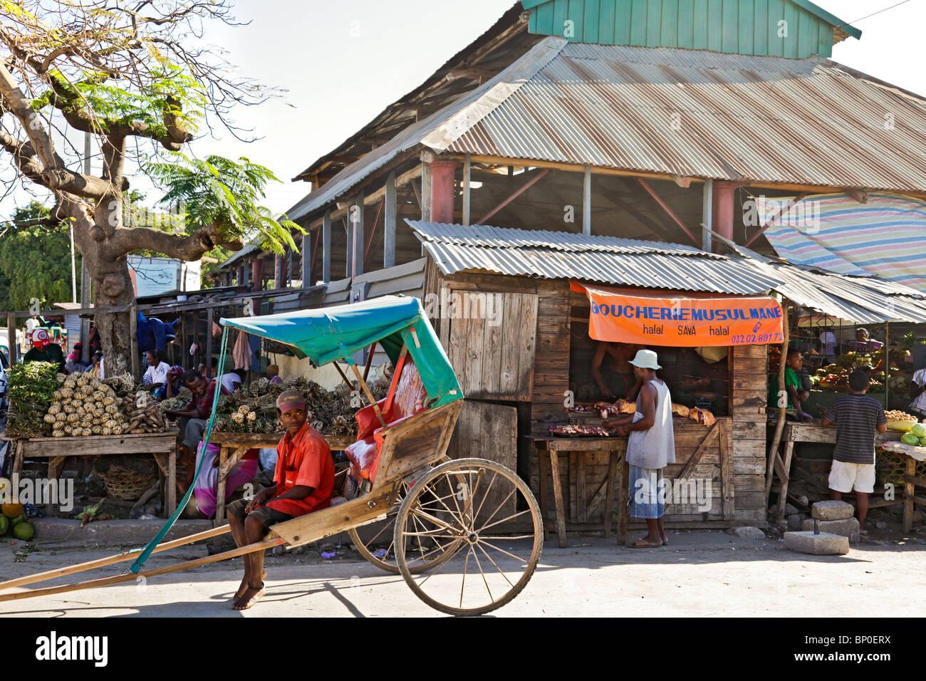 Pousse-pousse risciò e autista fuori un Halal macelleria nel mercato di Toliara / Toliary / Tulear, a sud-ovest Immagini Stock