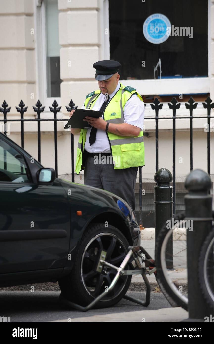 Un vigile emette un biglietto prima del distacco di un illegalmente auto parcheggiata da un alloggiamento per disabili Immagini Stock